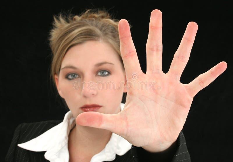 Mujer de negocios hermosa con la palma de la mano hacia fuera delante de ella fotografía de archivo libre de regalías