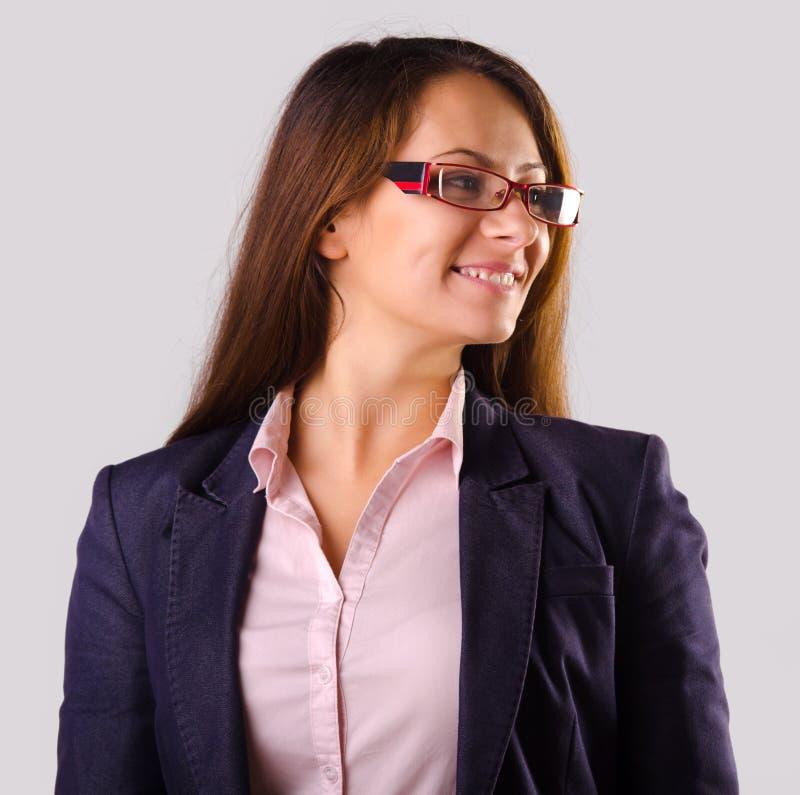 Mujer de negocios hermosa con los vidrios aislados en gris imagenes de archivo