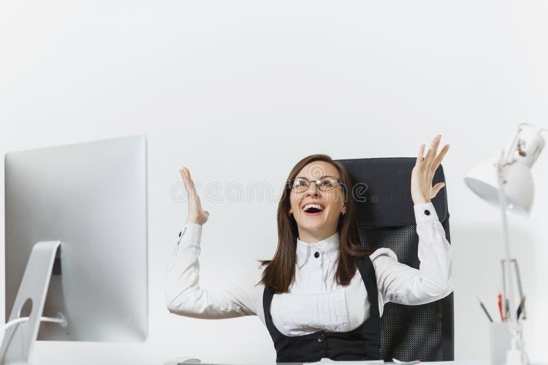 Mujer de negocios hermosa en el funcionamiento del traje y de vidrios en el ordenador con los documentos en oficina ligera foto de archivo