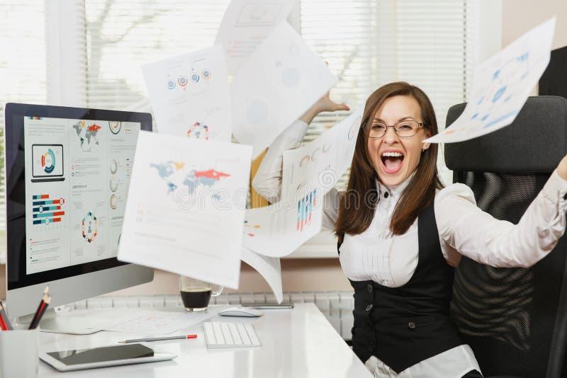 Mujer de negocios hermosa en el funcionamiento del traje y de vidrios en el ordenador con los documentos en oficina ligera imagenes de archivo