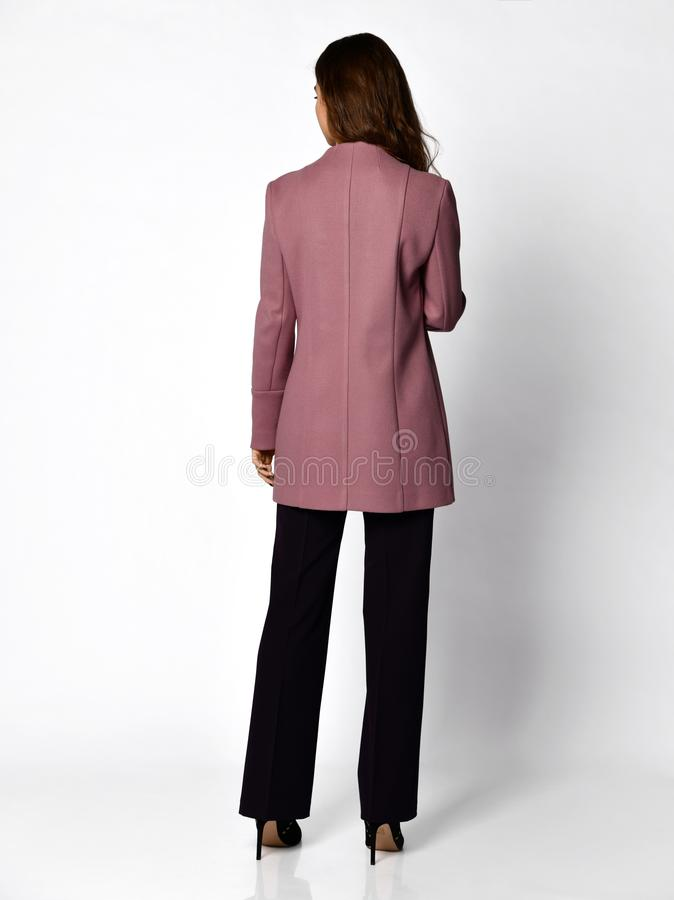 Mujer de negocios hermosa joven que camina en traje púrpura de la nueva primavera casual del diseño en gris imagen de archivo libre de regalías