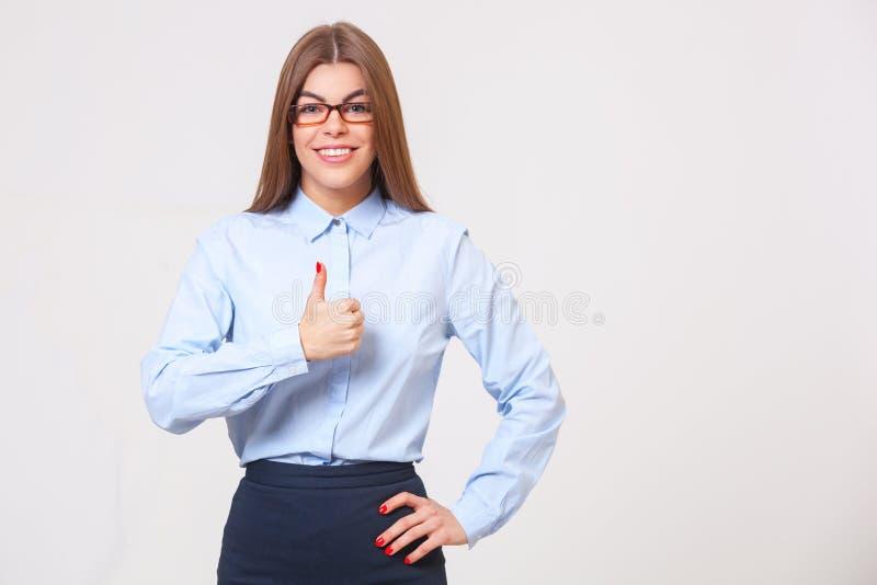 Mujer de negocios hermosa joven que muestra los pulgares encima de la muestra aislada fotografía de archivo