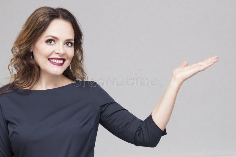 Mujer de negocios hermosa joven sonriente feliz que muestra el área en blanco para la muestra o el copyspase, aislada sobre fondo imagen de archivo