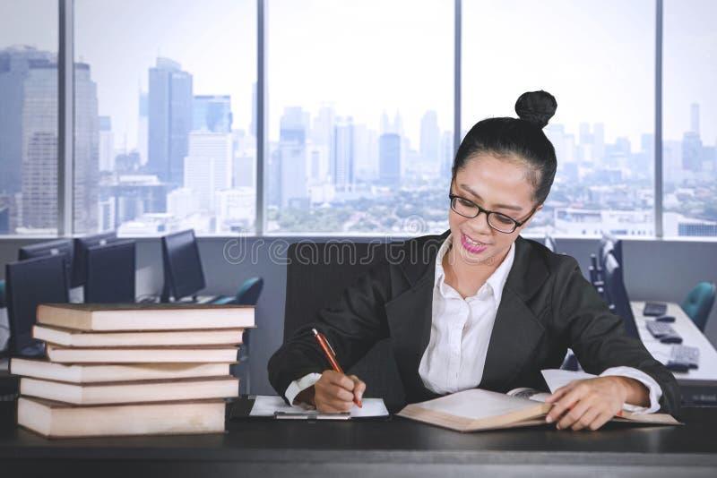 Mujer de negocios hermosa que escribe en un tablero imagen de archivo