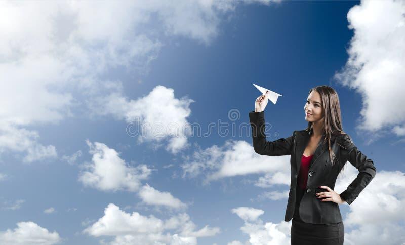 Mujer de negocios que lanza un avión de papel imágenes de archivo libres de regalías