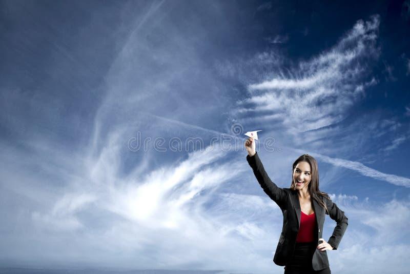 Mujer de negocios que lanza un avión de papel fotos de archivo