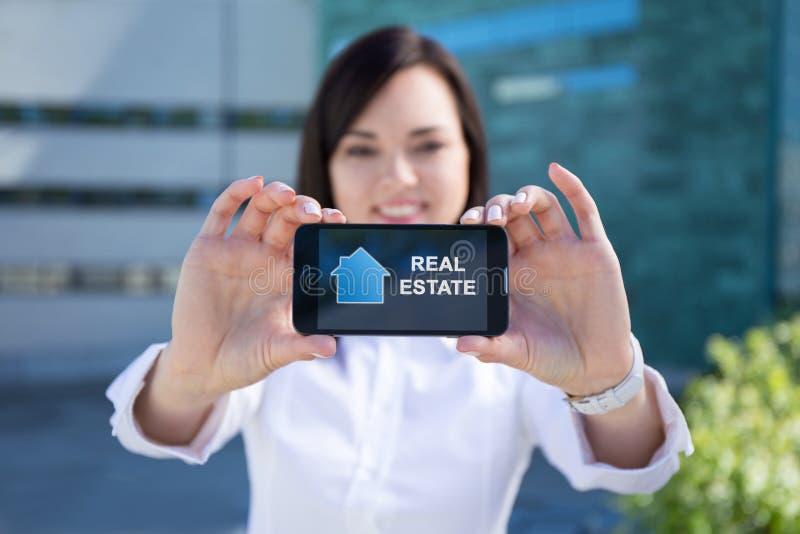 Mujer de negocios hermosa que muestra smartphone con las propiedades inmobiliarias app imagen de archivo
