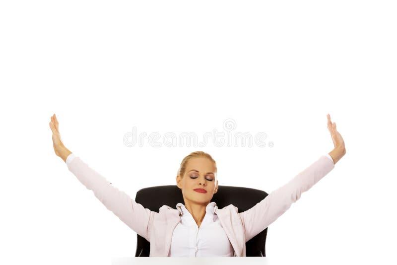 Mujer de negocios hermosa que se sienta detrás del escritorio y que estira sus brazos fotos de archivo