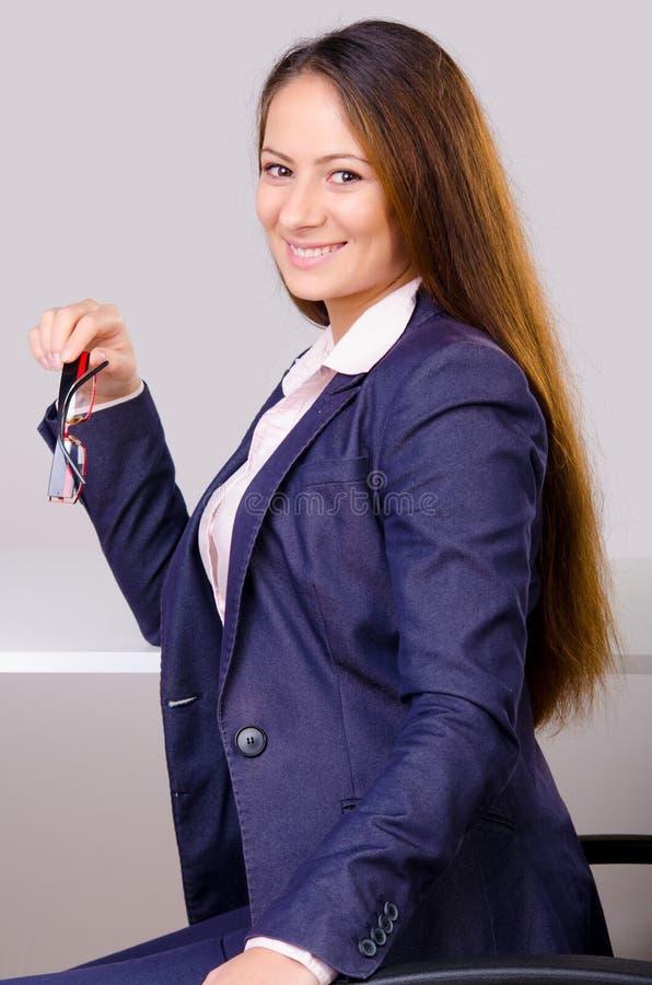 Mujer de negocios hermosa que se sienta en su escritorio fotografía de archivo