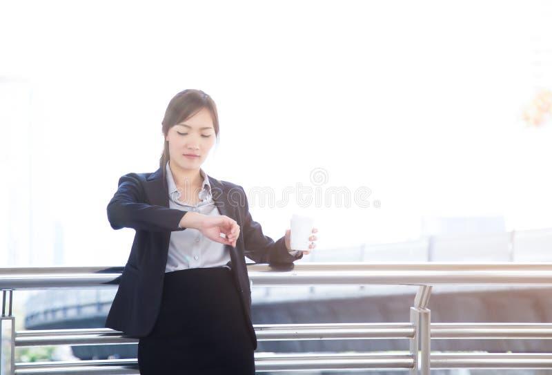 Mujer de negocios hermosa que sostiene una taza de café y que comprueba el th imagenes de archivo