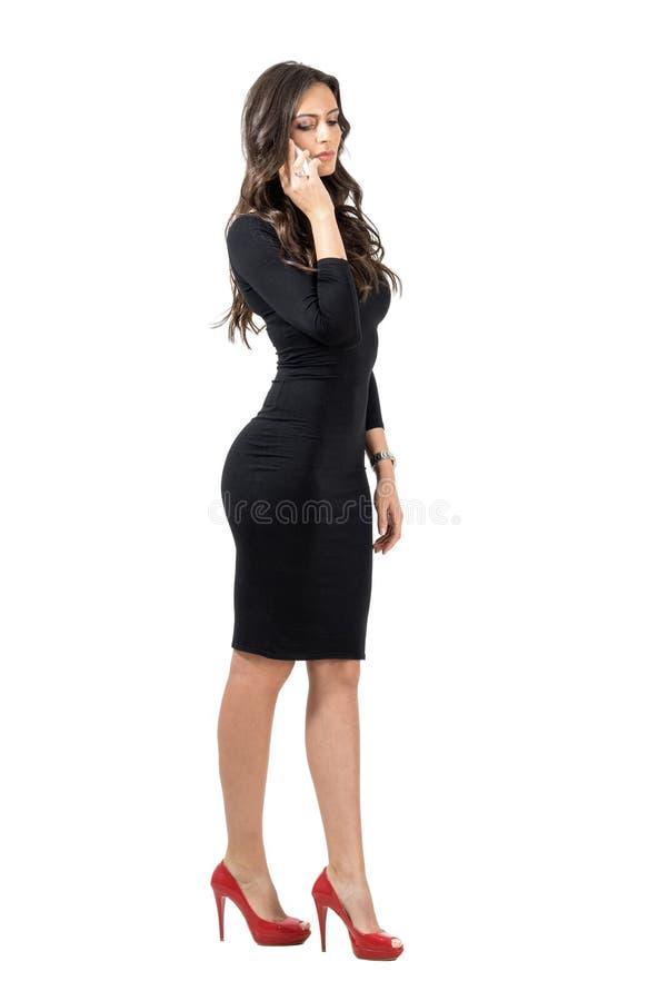 Mujer de negocios hispánica elegante que mira abajo mientras que habla en el teléfono elegante foto de archivo