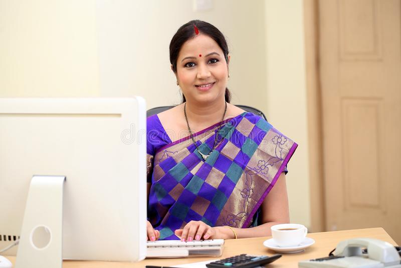 Mujer de negocios india tradicional feliz en el escritorio de oficina imágenes de archivo libres de regalías