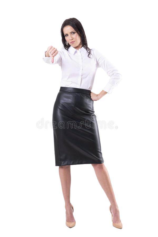 Mujer de negocios infeliz descontentada en el pulgar de cuero de la demostraci?n de la falda abajo del gesto y mirada de la c?mar foto de archivo