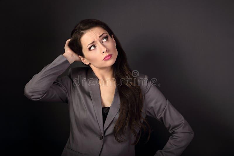 Mujer de negocios infeliz seria en el traje que mira para arriba y o de pensamiento fotografía de archivo