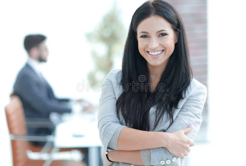 Mujer de negocios joven acertada en el fondo de la oficina fotografía de archivo