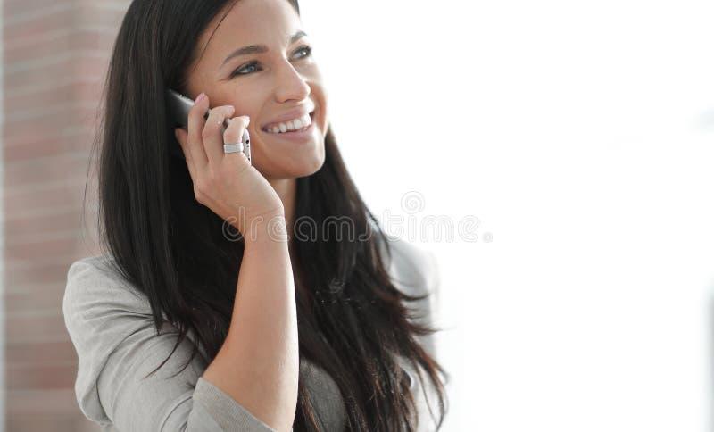 Mujer de negocios joven acertada que habla en un smartphone imagen de archivo