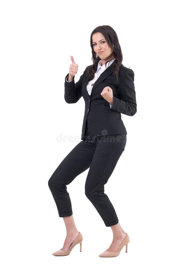 Mujer de negocios joven acertada que se agacha celebrando triunfo con el pulgar para arriba foto de archivo