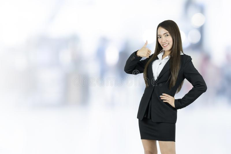 Mujer de negocios joven asiática sonriente con el pulgar para arriba imagen de archivo