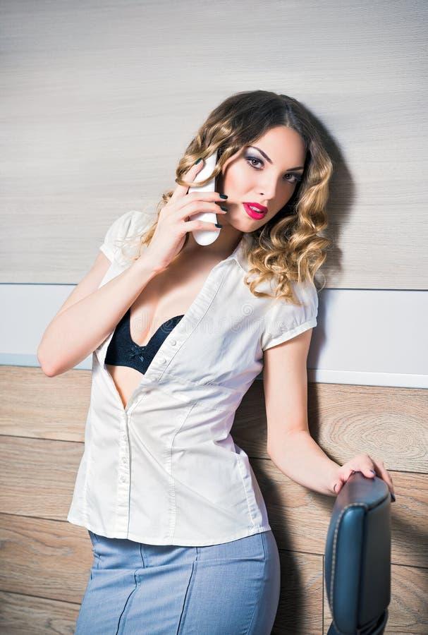 Mujer de negocios joven atractiva que habla en el teléfono imagenes de archivo
