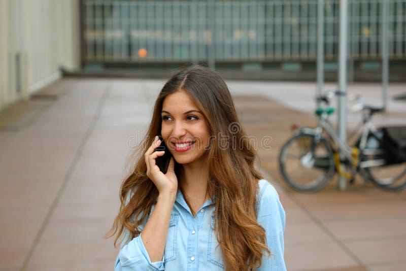 Mujer de negocios joven atractiva que habla en su teléfono mientras que se coloca en el patio de los bloques de oficina Mujer de  foto de archivo libre de regalías
