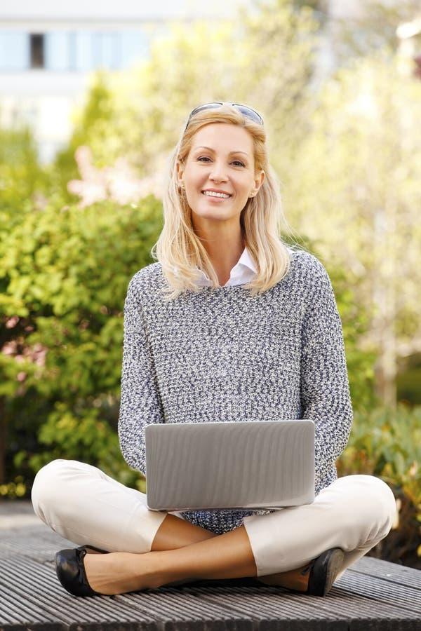Mujer de negocios joven atractiva que se sienta en silla y el trabajo de la barra fotos de archivo