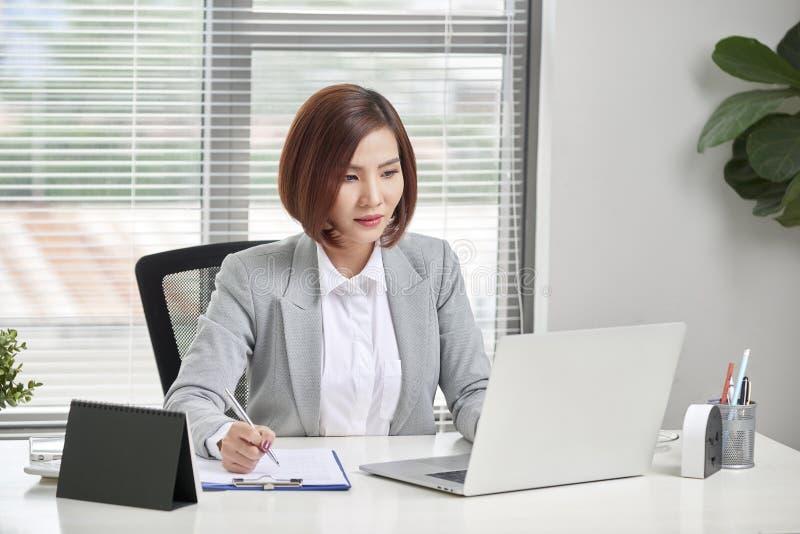 Mujer de negocios joven, atractiva y confiada que trabaja en oficina fotos de archivo libres de regalías