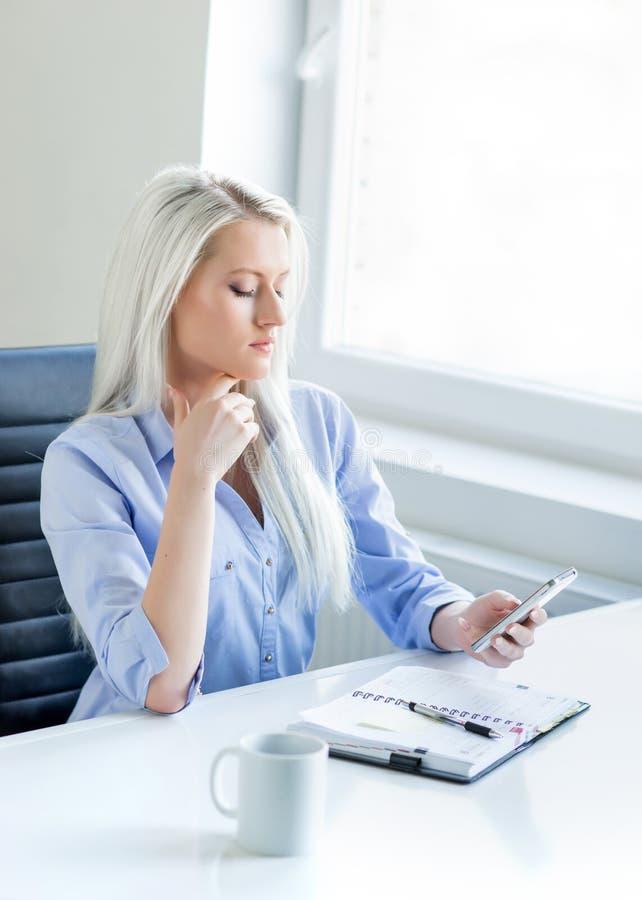 Mujer de negocios joven, atractiva y confiada que trabaja en oficina imagen de archivo libre de regalías