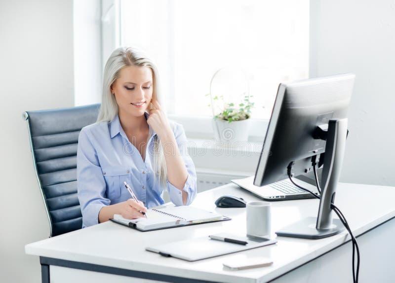 Mujer de negocios joven, atractiva y confiada que trabaja en oficina fotografía de archivo libre de regalías