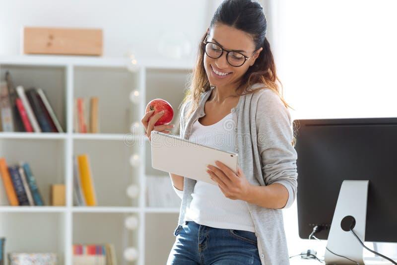 Mujer de negocios joven bonita usando su tableta digital mientras que come la manzana roja en la oficina imagenes de archivo
