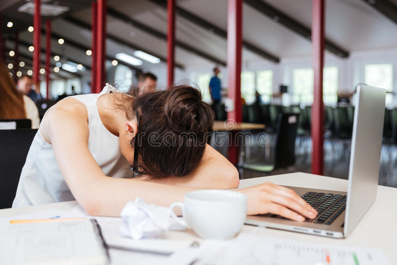 Mujer de negocios joven cansada agotada que duerme en la tabla en el lugar de trabajo imágenes de archivo libres de regalías