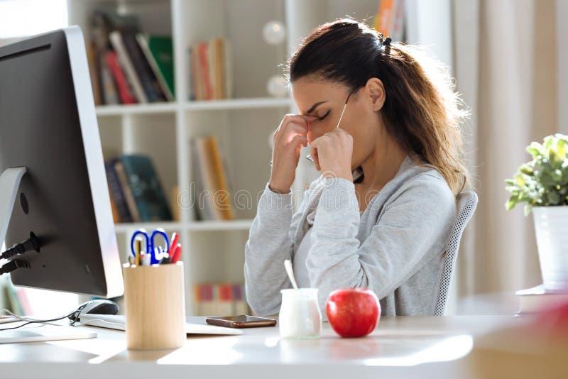 Mujer de negocios joven cansada que tiene dolor de cabeza mientras que trabaja con el ordenador en la oficina foto de archivo libre de regalías