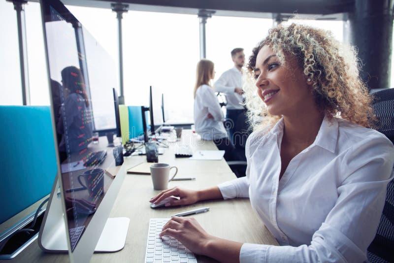 Mujer de negocios joven con el ordenador en la oficina imagenes de archivo