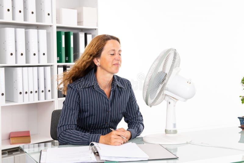 Mujer de negocios joven con el ventilador en su escritorio en o summerly caliente foto de archivo