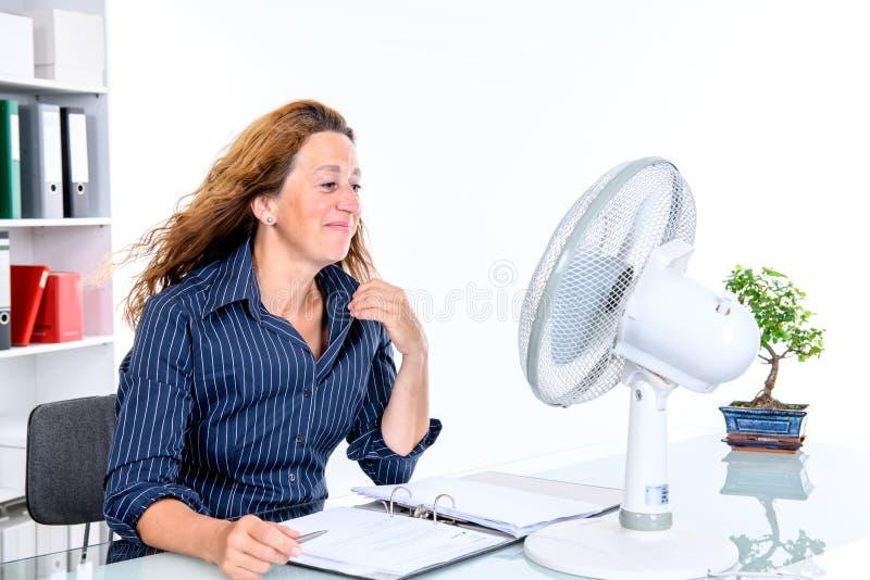Mujer de negocios joven con el ventilador en su escritorio en o summerly caliente foto de archivo libre de regalías