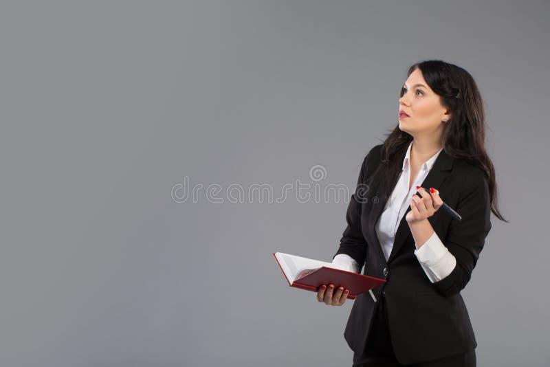 Mujer de negocios joven con la libreta y pluma cerca de su barbilla Escritura pensativa de la señora del negocio en el tablero qu fotos de archivo libres de regalías