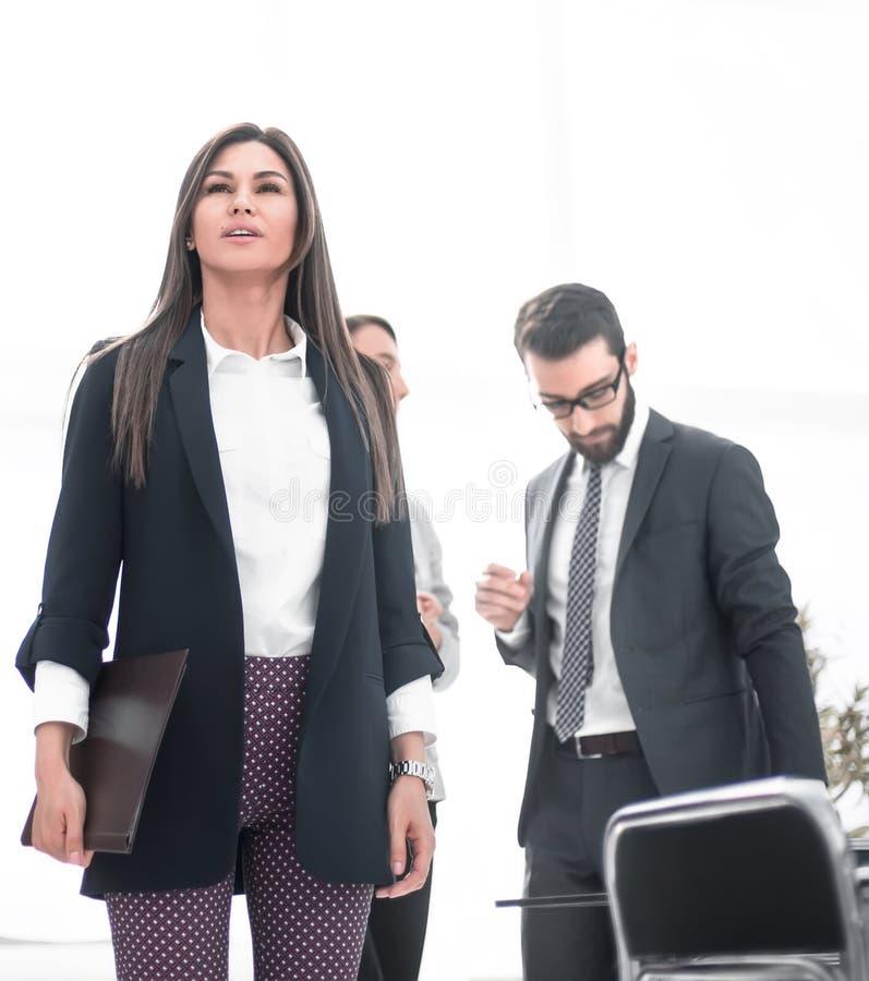 Mujer de negocios joven con los documentos que se colocan en la oficina imagen de archivo