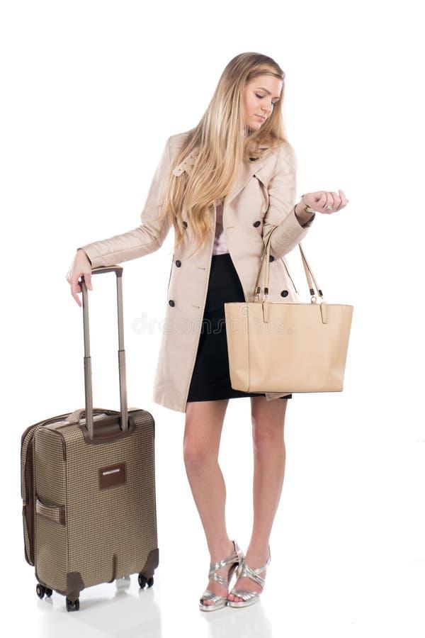 Mujer de negocios joven con su bolso y maleta listos para viajar imagenes de archivo