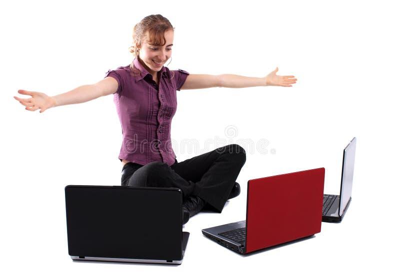 Mujer de negocios joven con tres computadoras portátiles fotografía de archivo
