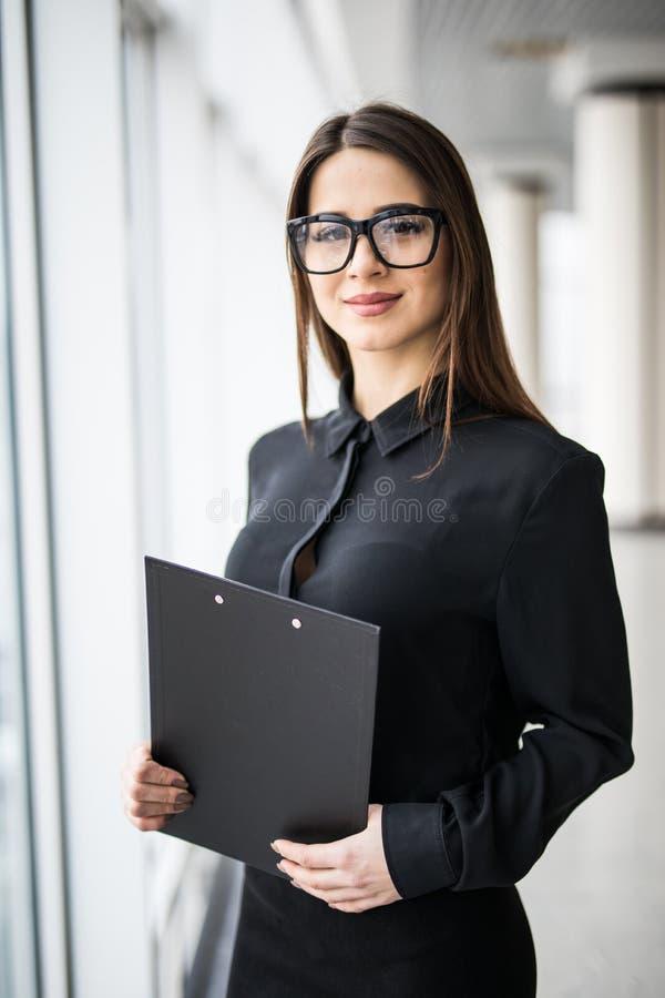 Mujer de negocios joven con una carpeta contra ventanas de la oficina fotografía de archivo libre de regalías