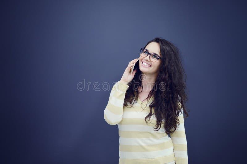 Mujer de negocios joven, confiada, acertada y hermosa con el teléfono móvil aislado imagen de archivo libre de regalías