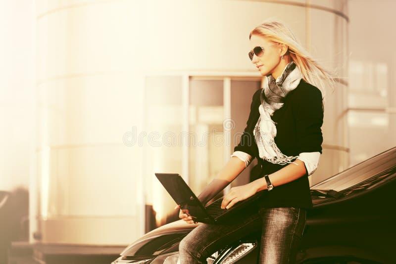 Mujer de negocios joven de moda con el ordenador portátil que se sienta en su coche foto de archivo libre de regalías