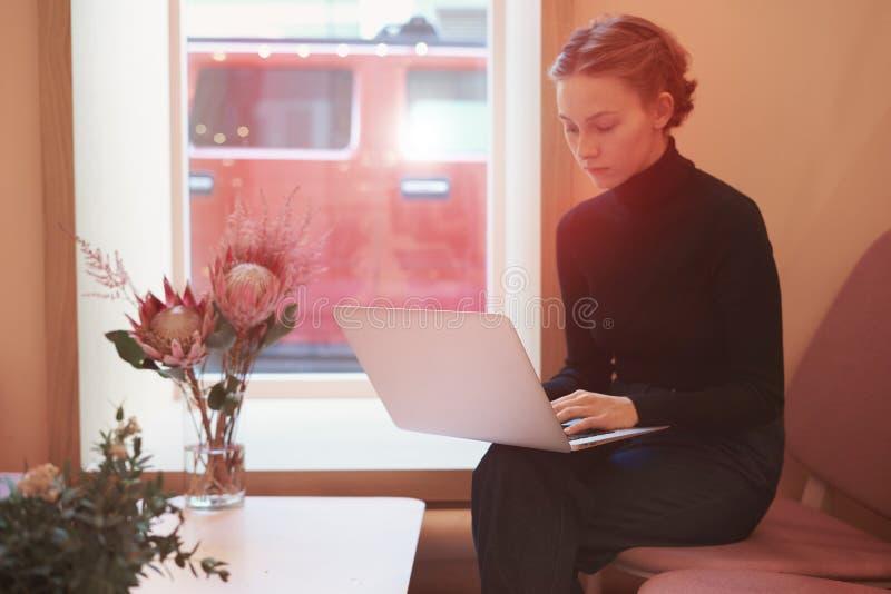 Mujer de negocios joven del inconformista que trabaja en el ordenador portátil, sentándose en café cerca de ventana, luz del día imágenes de archivo libres de regalías