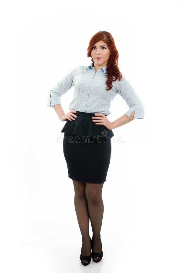 Mujer de negocios joven del pelirrojo con la mano en la cintura imágenes de archivo libres de regalías