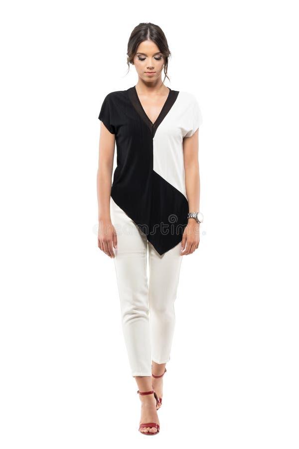 Mujer de negocios joven elegante en traje blanco y negro que camina y que mira abajo imagenes de archivo