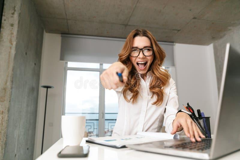 Mujer de negocios joven emocionada vestida en camisa formal de la ropa dentro usando el ordenador portátil que señala a usted imagen de archivo
