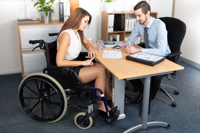 Mujer de negocios joven en el funcionamiento de la silla de ruedas con un colega masculino en la oficina imagenes de archivo