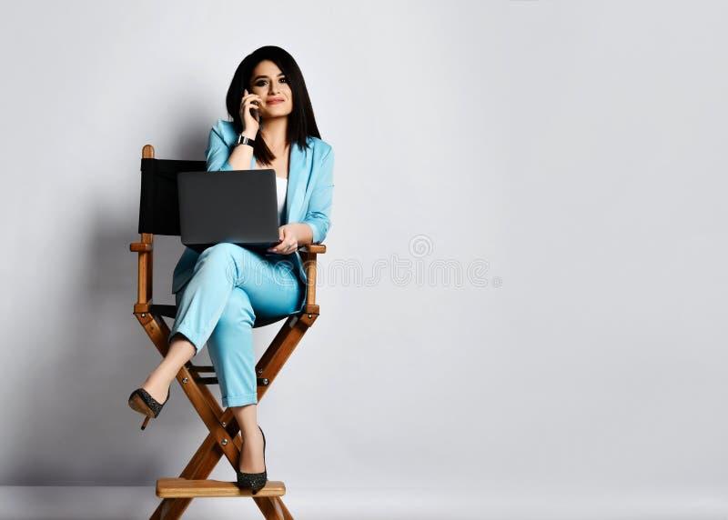 Mujer de negocios joven en el pantsuit oficial azul que se sienta con el ordenador portátil en la alta butaca de madera y que hab fotografía de archivo