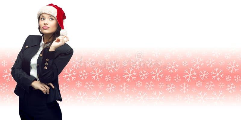 Mujer de negocios joven en el sombrero de santa que se coloca sobre backgroun del invierno fotografía de archivo