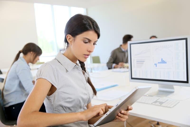Mujer de negocios joven en la tableta en la oficina imagenes de archivo
