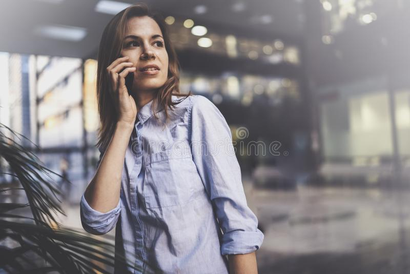 Mujer de negocios joven encantadora que habla con el socio vía el teléfono móvil mientras que se coloca en el centro de negocios  fotos de archivo libres de regalías